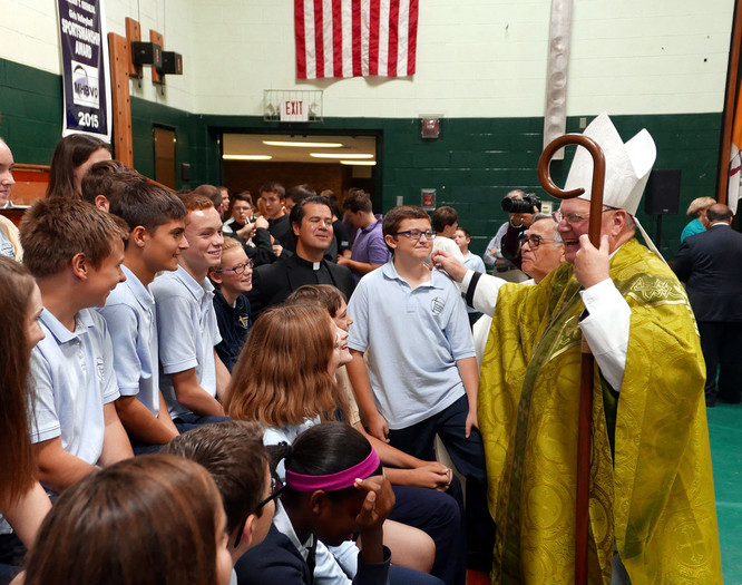 Cardinal Dolan laughs along with John A. Coleman Catholic High School students in the gymnasium on Oct. 3. Father Robert Bubel, pastor of St. Mary-Holy Name of Jesus and St. Peter's in Kingston, is pictured in the center of the students.