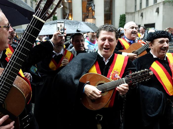 MARCHA UNIDA—La lluvia no apaciguo el espíritu de quienes marcharon en el desfile del Día de la Hispanidad por la quinta avenida el 9 de octubre. En la foto un grupo de España incluyendo a un hombre con un laud de mano, y quien toca mientras marchan.