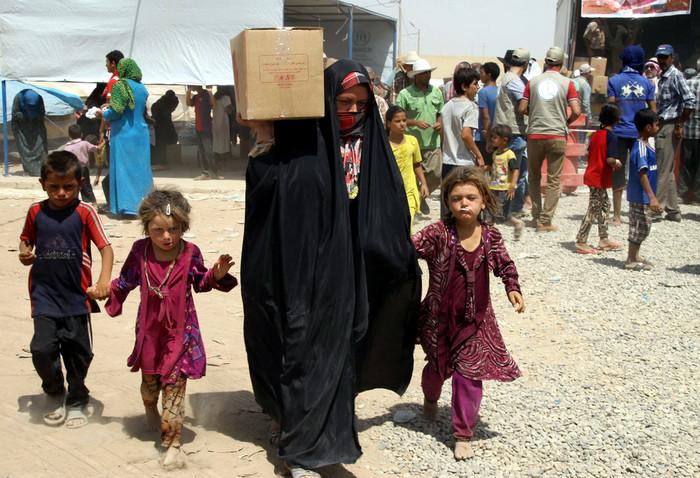 """FAMILIA DESPLAZADA—  Una mujer iraquí lleva una carga de ayuda humanitaria junto a sus hijos el 23 de diciembre en un campamento para personas desplazadas cerca de Irbil, Irak. """"Creando una Cultura de Encuentro"""" es el tema de la Semana Nacional de la Migración del 2017, una observación anual que los Obispos Católicos de los Estados Unidos comenzaron hace más de 25 años."""