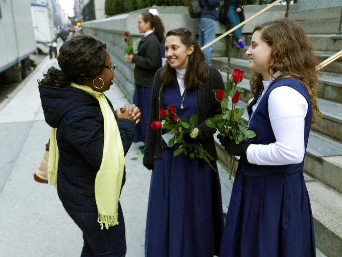 Julie Martin and Karalyn Finnero, both postulants with the Sisters of Life, invite a passerby outside St. Patrick's Cathedral to the Day for Life inside St. Patrick's Cathedral on Jan. 21.
