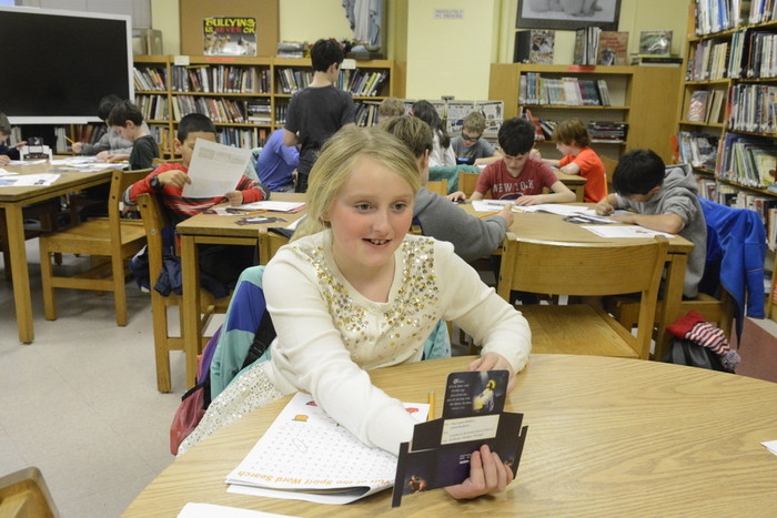 Brooke Thompson, a fourth-grader in the religious education program at St. Joseph's in Bronxville, holds a Lenten offering box that is personalized with the name of a child from Cristo del Rosario parish in Managua, Nicaragua.