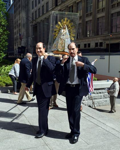 Varios hombres llevan cuidadosamente la estatua de Nuestra Señora de Luján afuera de la catedral.