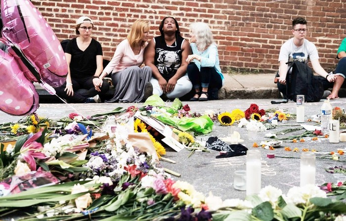 ANGUISH—People sit by a memorial of flowers in Charlottesville, Va., Aug. 14 where an Aug. 12 car attack took place against counter-protesters demonstrating at a rally of white nationalists.