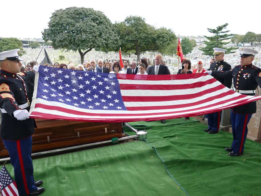 REMEMBERING A HERO—Members of the U.S. Marine Corps fold an American flag to present to the family of U.S. Marine Corps Pvt. Joseph Carbone at his burial at Calvary Cemetery in Queens Sept. 30. Carbone, who grew up in Brooklyn, died in World War II's Battle of Tarawa in November 1943 and returned home for burial after a DNA match with his niece Nancy Lewis of Brooklyn.