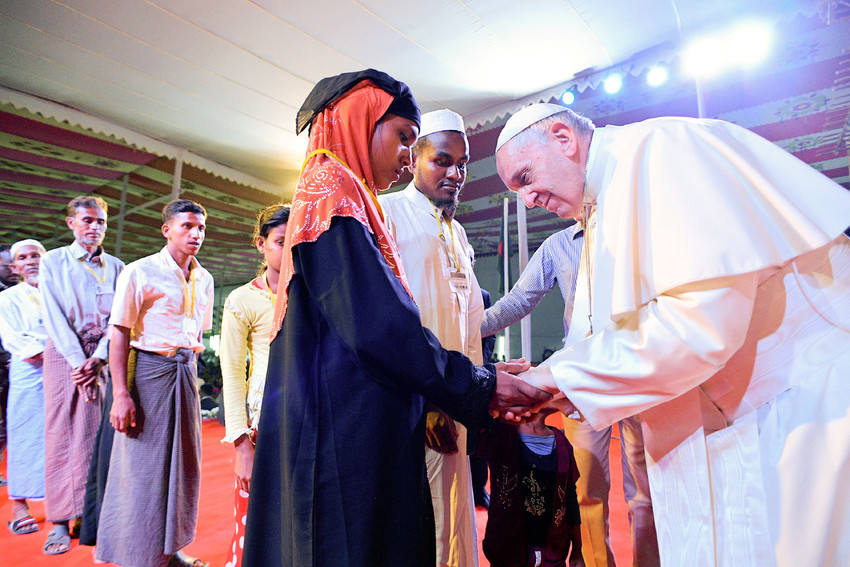 Pope Francis meets a young Rohingya refugee from Myanmar, above, during a Dec. 1 interreligious and ecumenical meeting for peace in the garden of the archbishop's residence in Dhaka, Bangladesh.