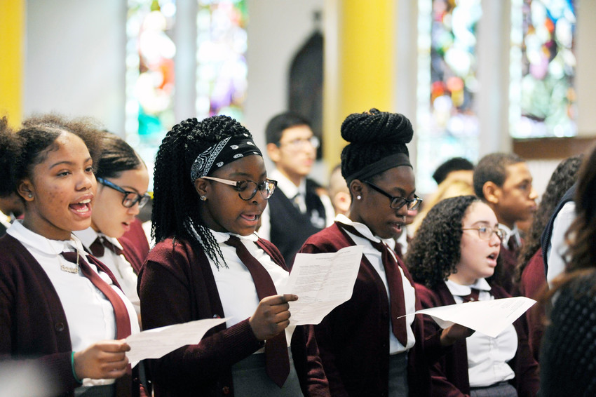 UNITED IN SONG—Serena Guzman, Chelsea Quansah and Marissa Suazo, students at St. Angela Merici School in the Bronx, were among 450 students from 15 Catholic schools in the Northwest/South Bronx Region to attend the Eighth-Grade Mass of Solidarity for Hurricane Victims at St. John Chrysostom Church in the Bronx Jan. 24. Catholic Schools Week runs until Feb. 3.