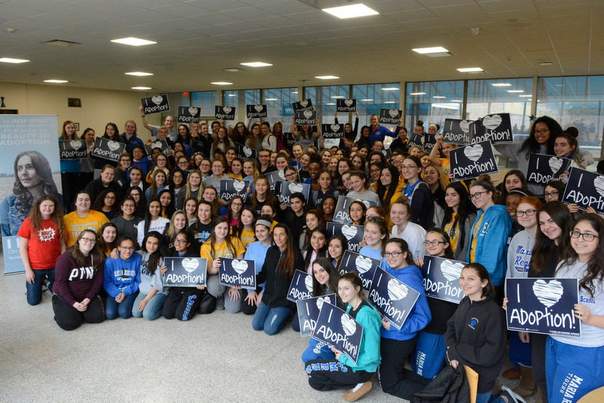 "Melissa Coles, kneeling, front row center, joins crowd of students at Maria Regina High School in Hartsdale Feb. 23. The students watched the documentary ""I Lived on Parker Avenue,"" a story about Mrs. Coles' choice of adoption over abortion."