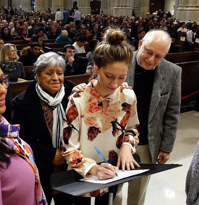 Francesca Marie Steward, a parishioner of Holy Family in New Rochelle, signs the Book of the Elect at the archdiocesan Rite of Election at St. Patrick's Cathedral Feb. 18. Ms. Steward's sponsors, Irma Palomino and Jerry Leiken, join her.
