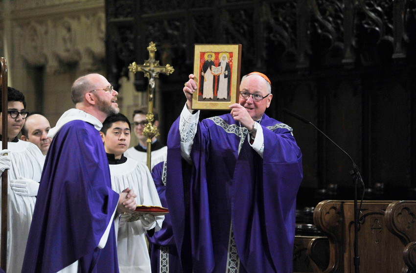 Cardinal Dolan displays an icon of St. Vincent Ferrer and St. Catherine of Siena at the vigil Mass he celebrated at St. Vincent Ferrer Church Feb. 17. Looking on is Father Walter Wagner, O.P., pastor of St. Vincent Ferrer and St. Catherine of Siena parish.