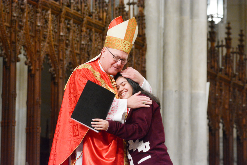 Cardinal Dolan hugs Leilani Aviles after the senior from the Academy of Mount St. Ursula in the Bronx delivered the word of gratitude to the cardinal near the end of the Mass for the Class of 2018 at St. Patrick's Cathedral April 23. About 1,900 students from 21 schools attended the first of two Masses honoring Catholic high school seniors in the archdiocese.