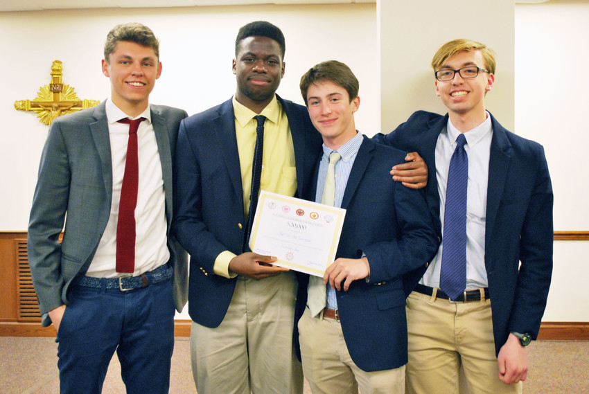 Fordham Prep seniors Jonah Shortall, Chike Odume, John Tomsen and Michael Tozzi, the winning team at the Ignatian Social Justice Tournament April 23, hold the first-place certificate.