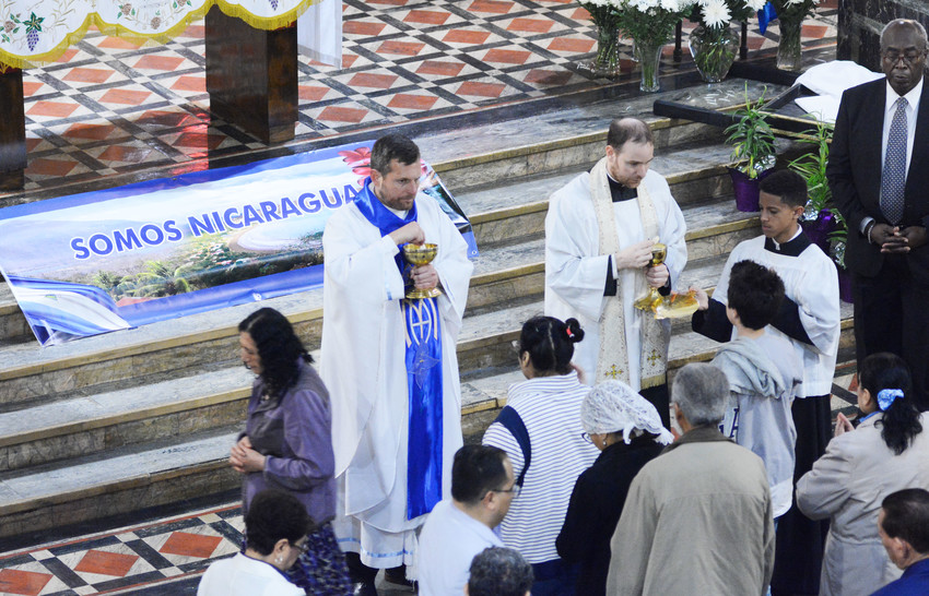 Father Enrique Salvo, pastor of St. Anselm and St. Roch parish in the Bronx, at left, and Father Patric D'Arcy, parochial vicar, administer Holy Communion during a special vigil Mass on April 28 at the church. The liturgy was dedicated for peace in Nicaragua, and for those who have died during the recent social violence there.