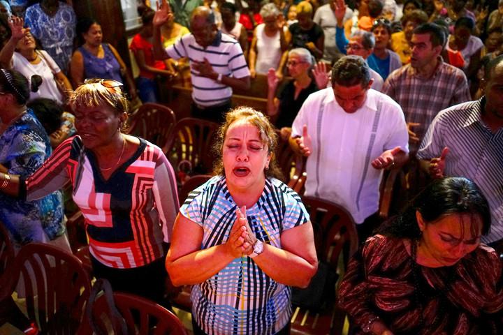 ORACIONES POR LAS VÍCTIMAS—Varias personas asisten a una vigilia de oración en una iglesia en La Habana el 20 de mayo para las víctimas del accidente aéreo del Boeing 737 que ocurrió dos días antes. Al menos 110 personas, entre ellas cinco niños, murieron en uno de los peores desastres aéreos en la historia de Cuba.