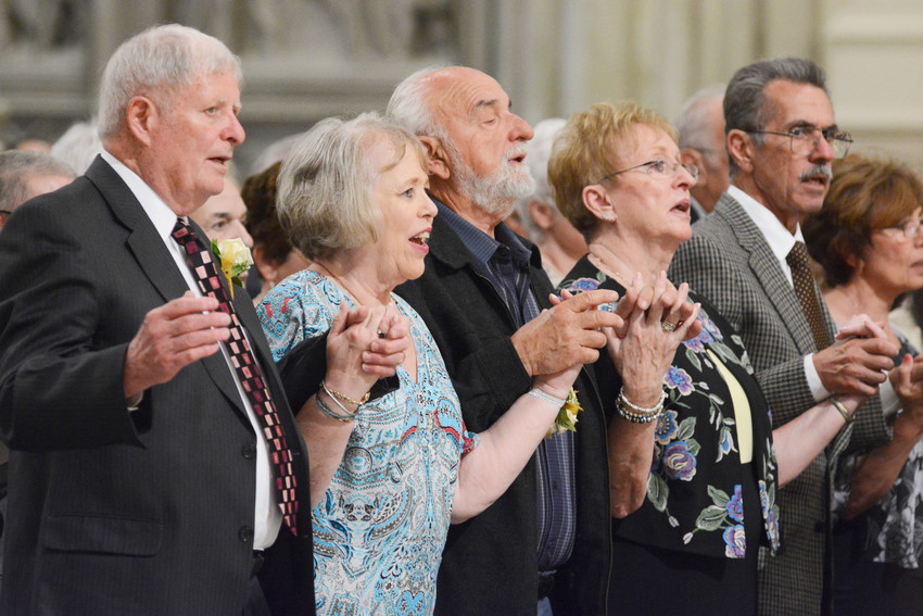 Married couples hold hands during the Lord's Prayer at the Golden Jubilee Mass celebrated by Cardinal Dolan at St. Patrick's Cathedral June 3. Family and friends filled the cathedral as 288 married couples celebrating their 50th wedding anniversary this year renewed their marriage vows.