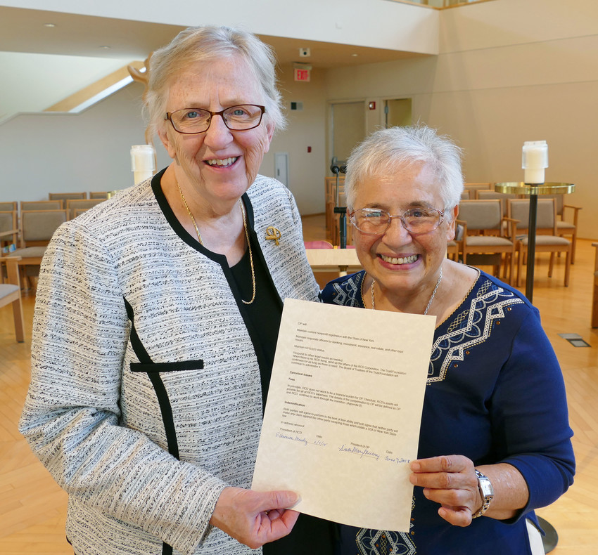 COMMITMENT—Sister Mary Murray, O.P., president of the Dominican Sisters of Sparkill, and Sister Veronica Mendez, R.C.D., president of the Sisters of Our Lady of Christian Doctrine, hold Covenant Relationship agreement, which they signed June 7 in Our Lady of the Rosary Chapel at Dominican Convent in Sparkill.