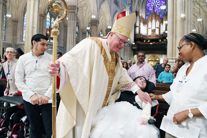The cardinal blesses Ashley Gonzalez, a resident of Specialty Hospital for Children at Terence Cardinal Cooke Health Care Center in Manhattan, as Marie Comberland, a certified nursing assistant, looks on.