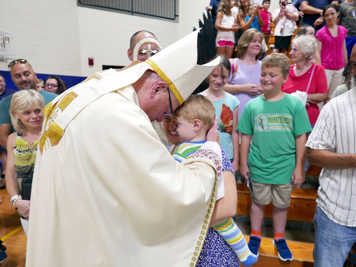 Cardinal Dolan greets 18-month-old William Sohl and his mother, Kodi Sohl.