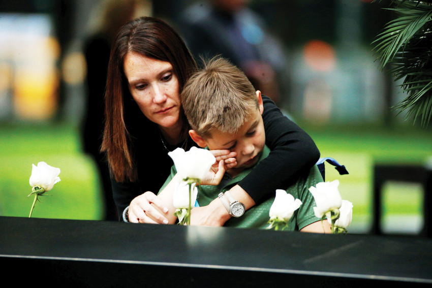 A woman and child place flowers at the National September 11 Memorial and Museum in Manhattan during Sept. 11 ceremonies to mark the 17th anniversary of the terrorist attacks at the World Trade Center. Nearly 3,000 people died in the attacks in New York City and Shanksville, Pa., and at the Pentagon.