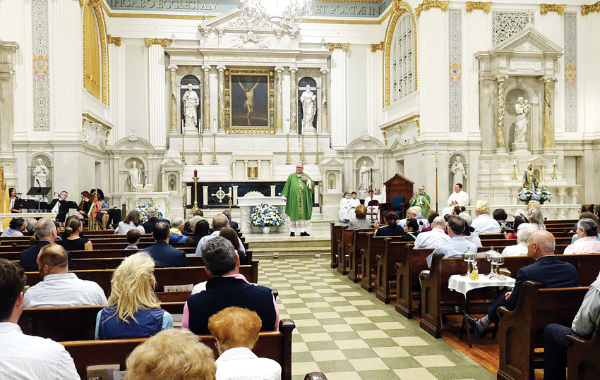 Cardinal Dolan addresses congregants at the historic St. Peter's Church in lower Manhattan during the Vigil Mass he celebrated Sept. 8. To the cardinal's right, in green chasuble, is Father Jarlath Quinn, pastor of St. Peter and Our Lady of the Rosary parish, who was a concelebrant.