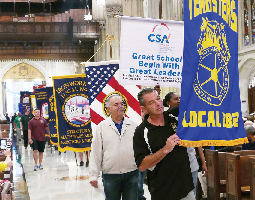 Union members parade up the aisle holding their banners at the start of the Labor Day Mass at St. Patrick's Cathedral Sept. 8.