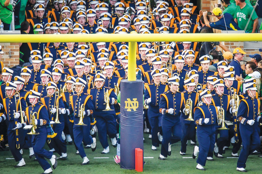 "The University of Notre Dame Marching Band runs onto the field before a college football game between the Fighting Irish and the University of Michigan at Notre Dame Stadium in South Bend, Ind., Sept. 1. The marching band is known for playing Notre Dame's ""Victory March"" fight song at athletic events."