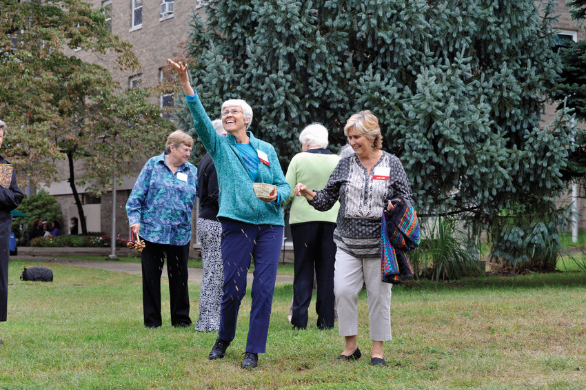 Sister Bette Ann Jaster, O.P., tosses seeds into the air at Mariandale following a Sept. 28 press conference in which the Dominican Sisters of Hope announced a conservation easement to prevent future development of 34 of the 61 acres on their Ossining property.