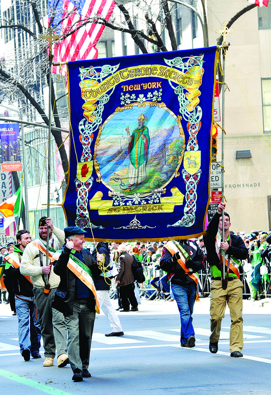 HONORING THE PAST—Celtic scrollwork surrounds image of St. Patrick on resplendent County Tyrone Society banner. Irish county societies usually carry ornate banners depicting saints and heroes.