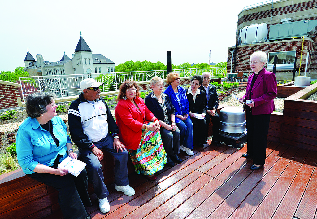 SPECIAL DAY—Sister Alice Marie Giordano, O.S.U., director of student volunteers at Serviam Gardens, meets with residents of the complex on its roof garden.
