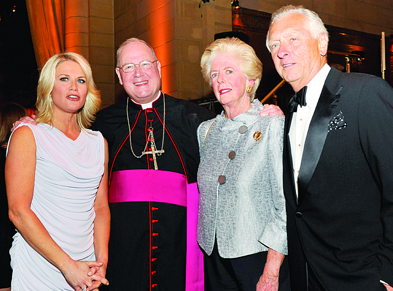 Archbishop Dolan greets news anchor Martha MacCallum, the master of ceremonies, and gala co-chairmen Mollie Callagy and John Callagy.