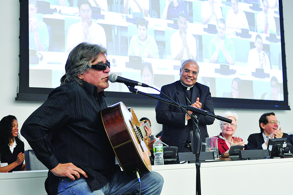 SPIRITED—Singer Jose Feliciano performs at the United Nations June 3 during event marking the International Year of Youth as Archbishop Francis A. Chullikatt, the Vatican nuncio to the U.N., applauds in the background.