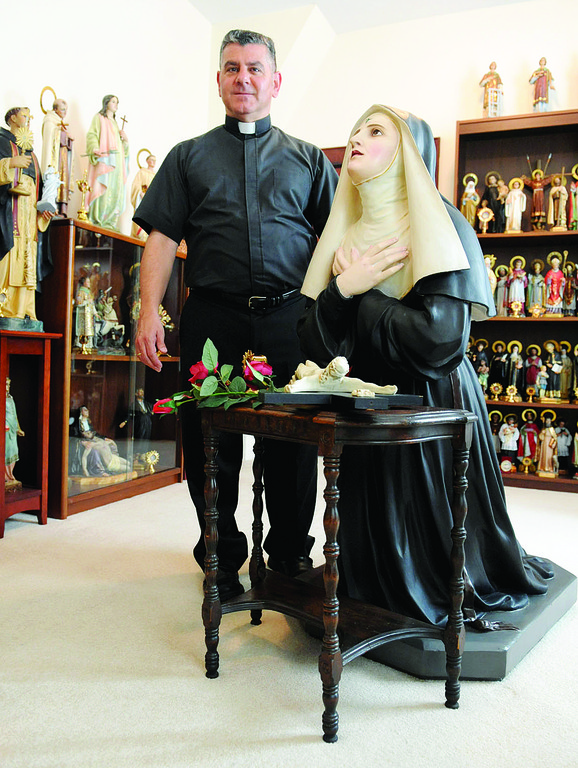 DEVOTION—Statues and relics from his collection surround Father Eugene Carrella,  pastor of St. Adalbert's on Staten Island, as he stands beside kneeling statue of St. Rita of Cascia. It had been in storage in a church in Buffalo for 30 years.