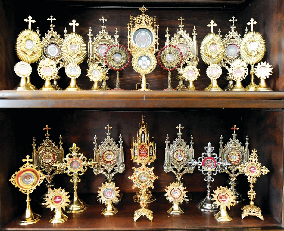 INSPIRATION AND HOPE—Relics are reverently displayed in gleaming reliquaries. Father Carrella bought a reliquary to house each relic in his collection; each is identified. He said that relics remind the faithful of their connection to the saints, who, like them, struggled to practice virtue, won the battle and attained heaven, and now intercede for those on earth.