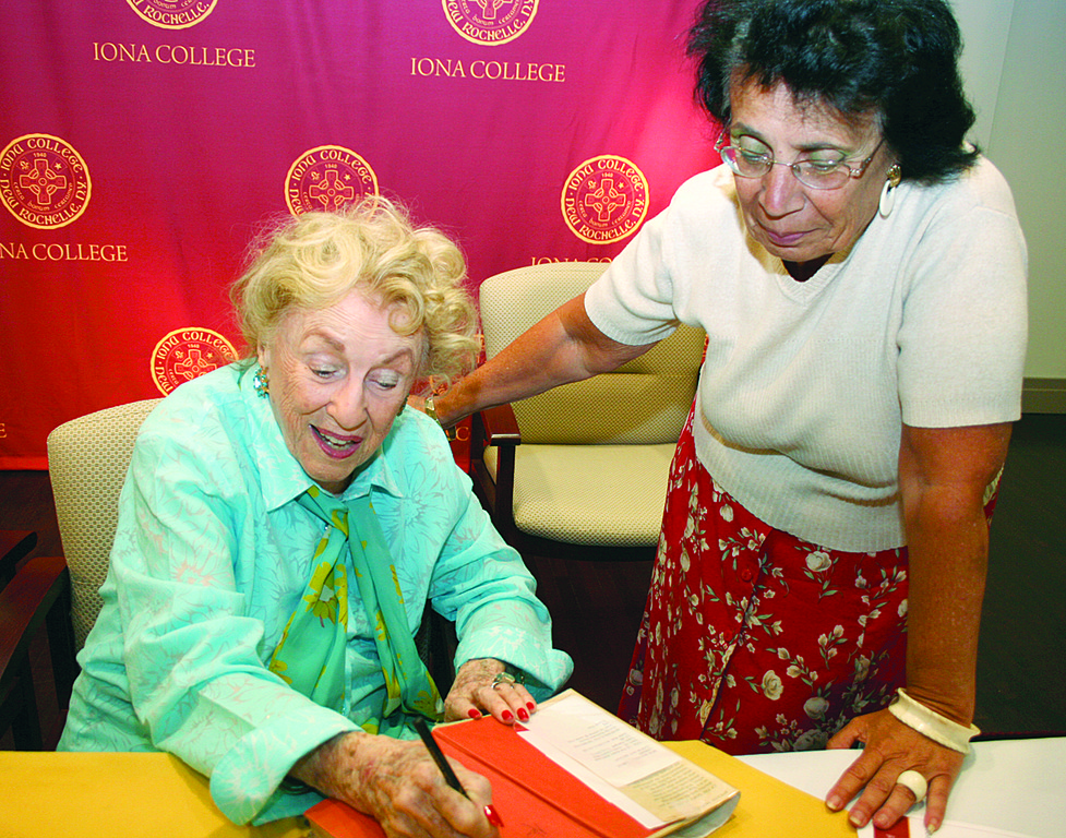 "GOOD REVIEW—Author Bel Kaufman signs an original copy of her book ""Up the Down Staircase"" for program participant Nancy Russo."