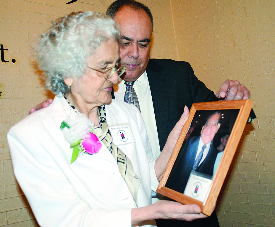 MOTHER AND SON—Marcelina Marrero, along with her son, Gabriel, looks lovingly at photograph of her husband of 74 years, Vicente, at World Marriage Day Mass. Vicente Marrero died two days before the Feb. 12 Mass at St. Patrick's Cathedral.