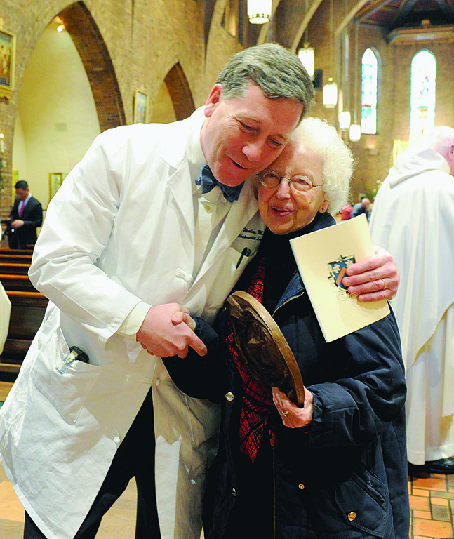 HEALING PRESENCE—Dr. John Healey, chief of orthopedic surgery at Memorial Sloan-Kettering Cancer Center, gives Sister Elaine Goodell, P.B.V.M., a big hug of congratulations after she received the St. Catherine of Siena Award for her 27 years of service as chaplain at Sloan Kettering.