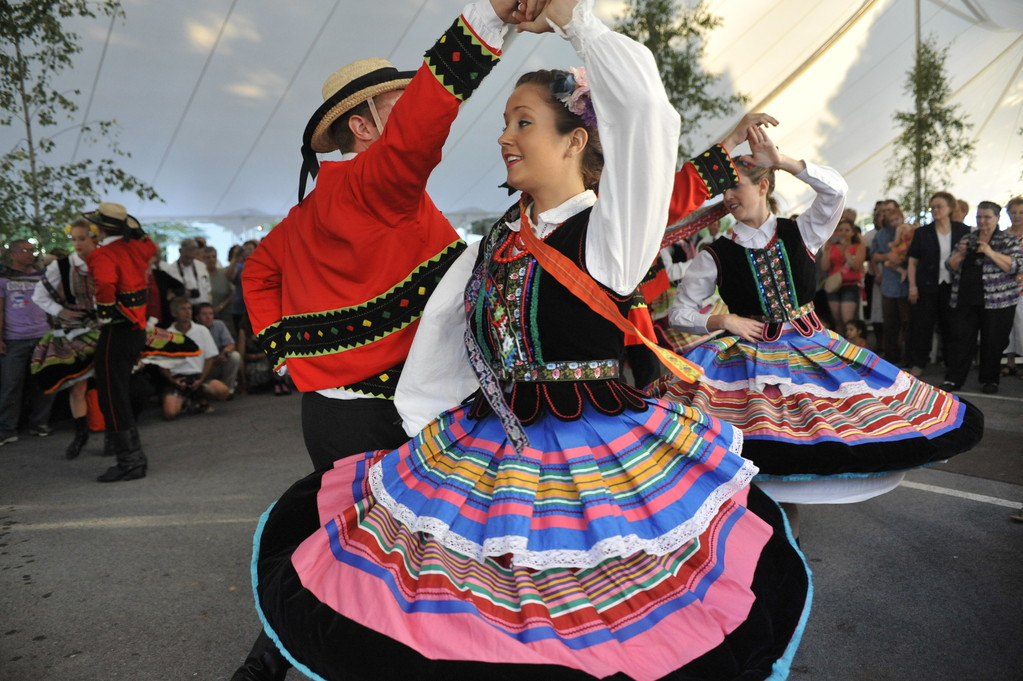 IN STEP WITH TRADITION—Pokolenie Dance Group member Rae Le Mieux twirls with partner, Tyler Murtie, after a Mass celebrated by Cardinal Dolan at St. Stanislaus Mission, Pine Island, in commemoration of the 100th anniversary. The group, wearing traditional Polish clothing, performed in a tent set up for a reception after the June 23 Mass. More than 800 people attended the Mass—with televisions set up in the parish hall and in the tent to accommodate the overflow crowd—with some 600 remaining for the reception.