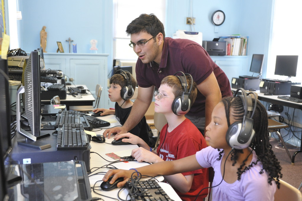BUILDING SKILLS—Andrew Newmark leads students Marcus Barone, James Sirico and Gabriele Richards through a computer program that builds literacy skills.
