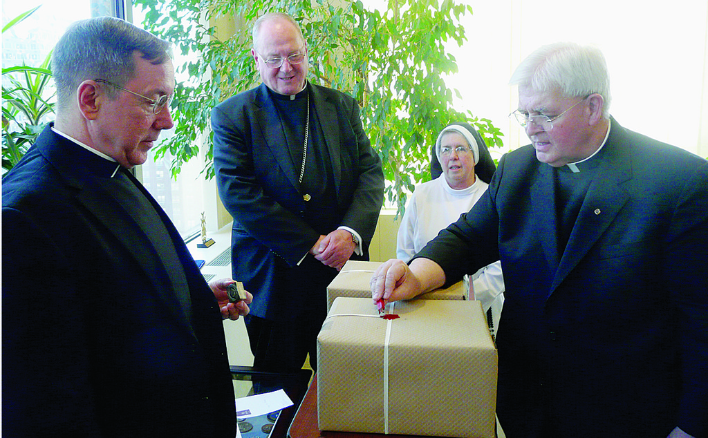 SEALED FOR DELIVERY—Father Gabriel O'Donnell, O.P., postulator for the sainthood cause of Rose Hawthorne Lathrop, seals packages of documents to be submitted to the Congregation for the Causes of Saints in Rome to support her canonization. At left is Msgr. Douglas Mathers, vice chancellor of the archdiocese. Cardinal Dolan looks on with Mother Mary Francis Lepore, O.P., superior general of the Dominican Sisters of Hawthorne, the order Rose Hawthorne Lathrop founded.