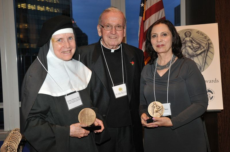 "AWARD WINNERS—Msgr. Peter Finn, member of the board of directors of The Christphers, presents the TV and Cable award to Mother Dolores Hart and her friend Judith Pinco for the HBO documentary ""God is the Bigger Elvis."" Mother Dolores, who is the subject of the documentary, accepted on behalf of Rebecca Cammisa, director and producer; Julie Anderson, producer; Sara Bernstein, supervising producer; and Sheila Nevins, executive producer."