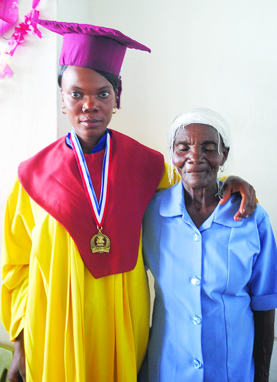 GRADUATION DAY—Lizana Sanon poses with her mother after her graduation, with evident pride on both of their faces.