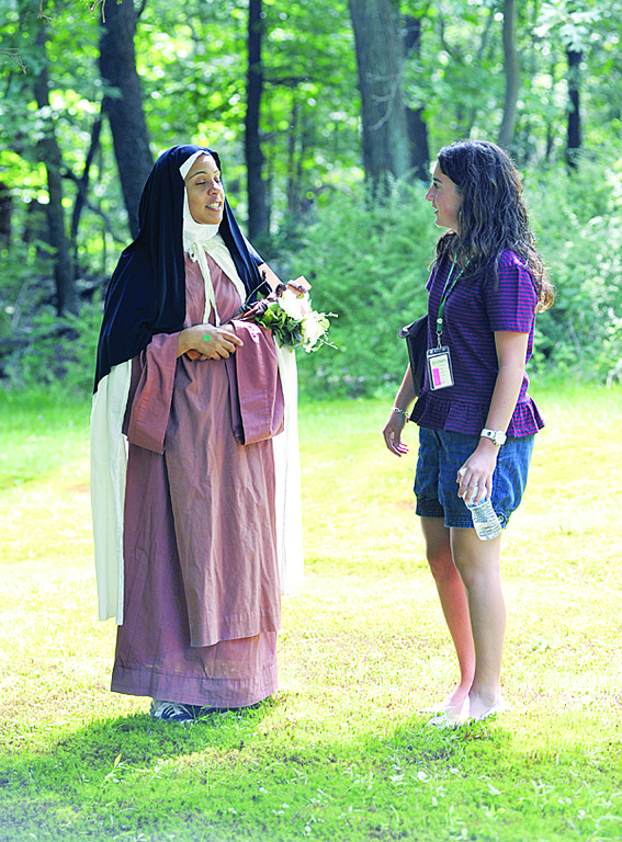 "Andrea Lifrieri listens to Ivy Marrero who is portraying St. Thérese of Lisieux in the ""Garden of the Saints."""