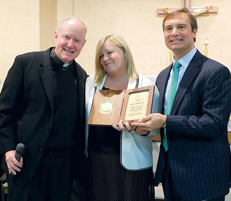 During an assembly, Father Timothy Scully, C.S.C., founder of ACE, presents an award to Christie and Tony deNicola for being distinguished supporters of educational excellence.