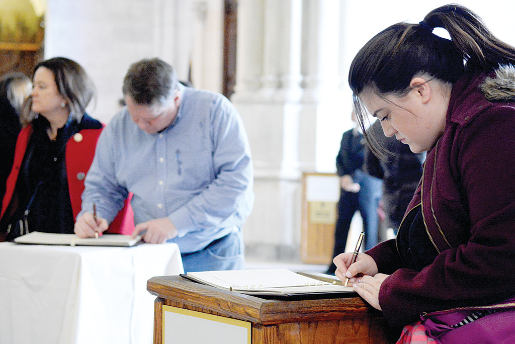 Visitors sign books of remembrance.