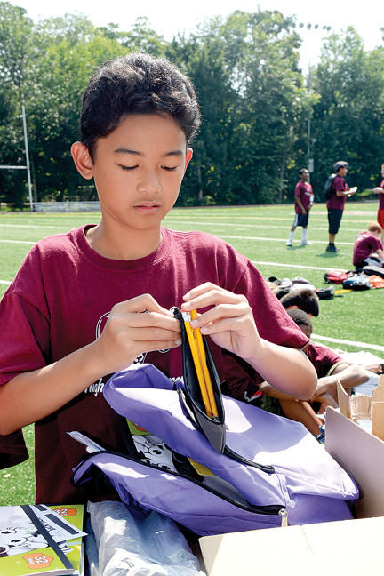 "Scott Castillo, a student in the Fordham Preparatory School Higher Achievement Program, fills a backpack with school supplies for prekindergarteners and kindegarteners in need for the program ""Operation Backpack"" on the Bronx school's track July 29."