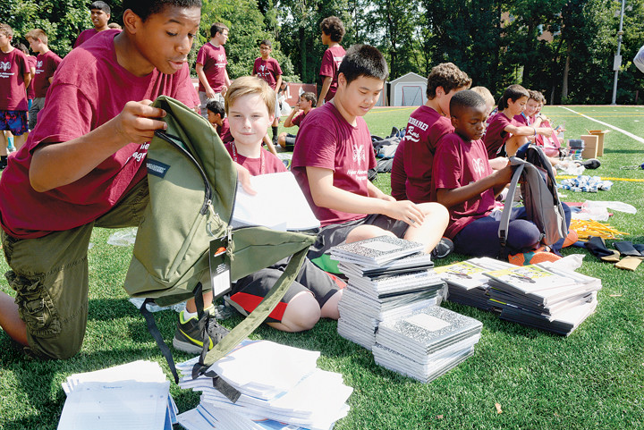 "Incoming eighth-graders in the Fordham Preparatory School Higher Achievement Program (HAP) team up to stuff backpacks for prekindergarten and kindergarten students as part of ""Operation Backpack."" The boys in the HAP program filled more than 1,000 bags at the Bronx school July 29 for distribution to children in need."