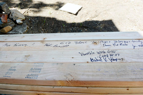 Velazquez signs a 2x4, to be used in the construction, with the words Possible with God, as Msgr. Keane watches.