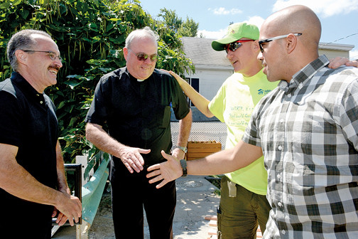 Deacon Nick Ramoni, far left, of St. John the Baptist parish in Yonkers; Msgr. Dennis Keane, pastor of Holy Family parish in New Rochelle and Jim Killoran, director of Habitat of Humanity of Westchester, greet Sgt. Velazquez Aug. 28.