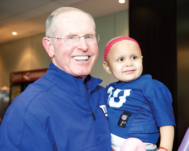 ALL SMILES—Giants Coach Tom Coughlin holds cancer patient Carmina at his foundation's Sundae Blitz. Every year, the team hosts children with cancer at their training center for a day of fun, frivolity and football apart from doctors, nurses and needles.