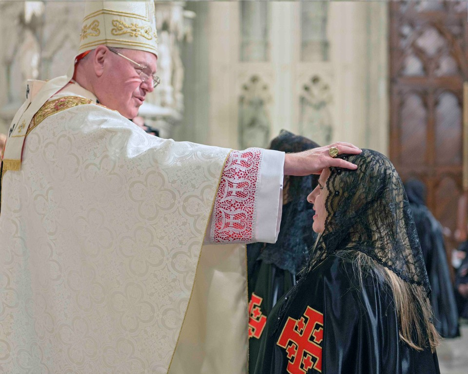 Cardinal Dolan makes sign of the cross on the forehead of a Lady to be promoted in the order.