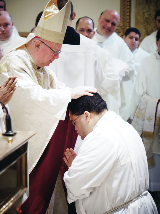 Bishop Murphy lays hands on Deacon Jean-Pierre Seon, who is studying to serve the Archdiocese of New York.